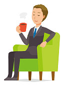 A young businessman is sitting on the sofa and drinking coffee