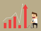 Young businessman pumps up a graph , Business concept