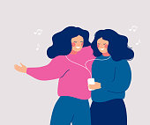 istock Young cheerful women sharing their earphone and listening to music with mobile phone and dancing. 1172669305