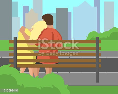 istock Young couple sitting on bench in the park 1212598440