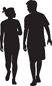 Vector silhouettes of a young couple walking together and looking at each other.