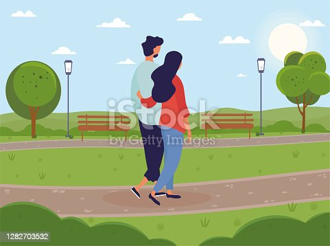 Young couple walking together in green park