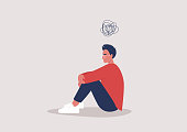 istock Young depressed male character sitting on the floor and holding their knees, a cartoon scribble above their head, mental health issues 1262705935