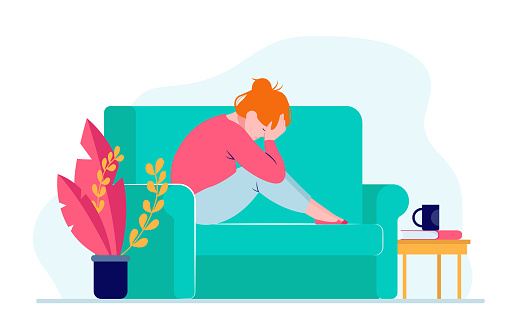 Young depressed woman sitting on sofa and holding head