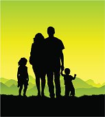 A young family together in the country. Full silhouettes including feet.