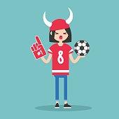 Young football fan wearing horned hat and foam finger