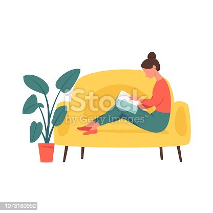 Young girl sitting in comfortable couch and and flipping through the magazine .