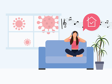 Young girl sitting on a sofa with headphones and listening to music. Stay Home Protect Yourself. Coronavirus outside. Coronavirus quarantine concept.