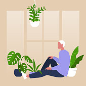 Young male character sitting by the window surrounded by house plants, meditative relaxation