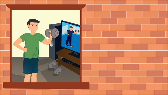 Young man does physical training exercises following lessons on smart tv at home during the coronavirus quarantine