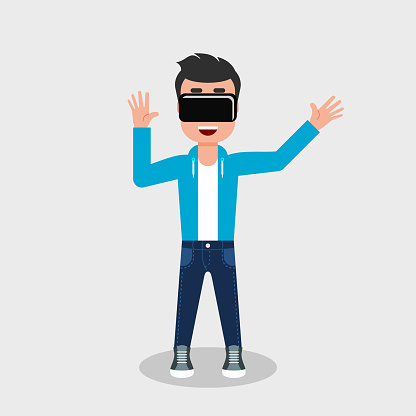 Young man in jeans and sweatshirt is looking through virtual reality glasses looking excited.