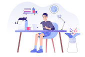 istock Young man or freelancer sitting on her a desk with cat and working online with a laptop at home illustration. Social distancing and self-isolation during corona virus quarantine. Vector illustration 1217246641