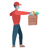 Young man wearing a medical mask and medical gloves to prevent the spread of the corona virus. Person going from the supermarket and holding grocery products in a bag. courier holds out a grocery bag.