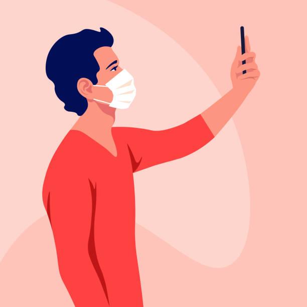 stockillustraties, clipart, cartoons en iconen met een jonge man draagt een medisch masker neemt een selfie en houdt smartphone in zijn hand. coronavirus. een blogger. epidemie en pandemie. - selfie