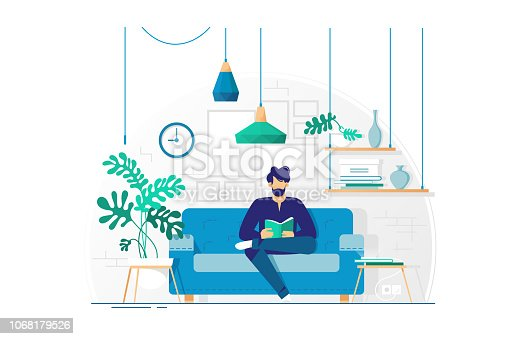 istock Young man with beard reading book sitting on couch. 1068179526