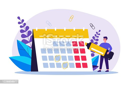 istock Young man with marker checking events in calendar 1226858977