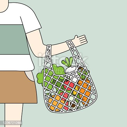 Young people stand holding net bag containing full of fresh organic fruits and healthy natural vegetables.