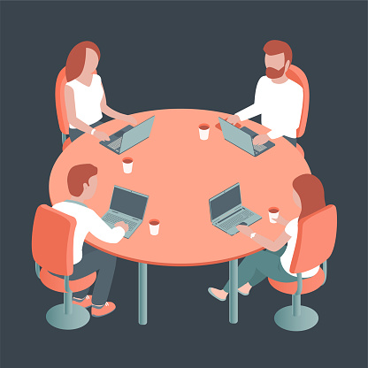 Young people with laptops are sitting at a round table in the office.