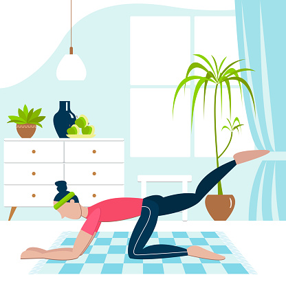 young woman in a shirt and leggings performs physical exercise while doing fitness at home in the room on a mat