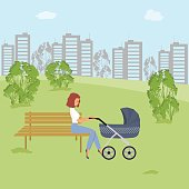 Young woman is sitting with a baby stroller on the bench in the park