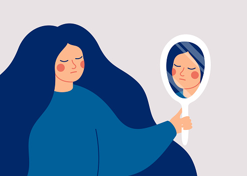 A young woman looks at her reflection in the mirror with sadness.