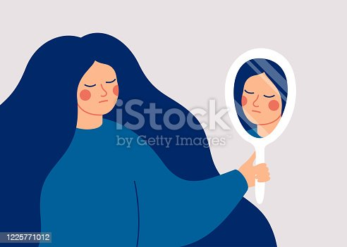 istock A young woman looks at her reflection in the mirror with sadness. 1225771012