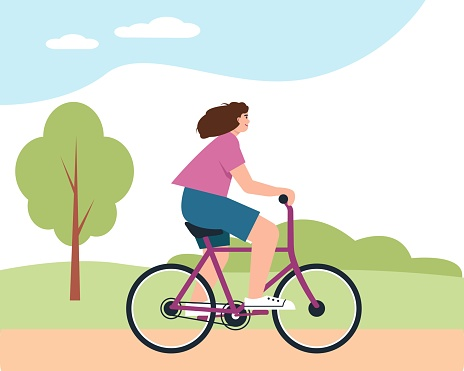 Young woman on bycicle in park. Smiling happy girl rides bike.