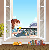 Young woman reading book in the window. Drinking tea and reading in the city.