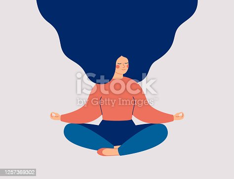 istock Young woman sits with cross-legged on the floor and meditates with closed eyes. 1257369302