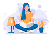 Young woman sitting cross-legged and read book.