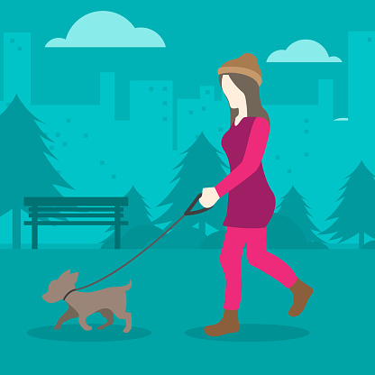 Young woman walking a dog in the park