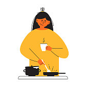 istock Young woman with coffee cup in hand cooking homemade meal frying in pan on stove 1320359195