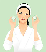 Young woman wearing a bathrobe with cucumber slices.