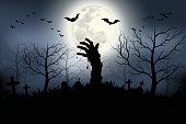 Zombie hands rising in dark Halloween night.