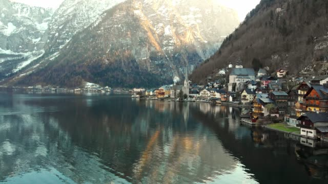 hallstatt - small village on the shore of hallstatter see under the steep slopes of dachstein mountains - австрия стоковые видео и кадры b-roll