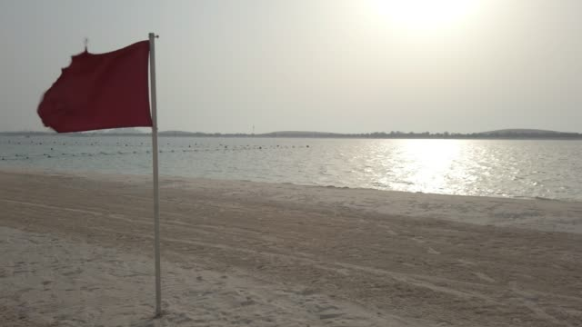 czerwona flaga na brzegu morza - niebezpieczeństwo - uae flag filmów i materiałów b-roll