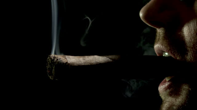 stockvideo's en b-roll-footage met cigar smoker on black-slow motion-1080hd - guy with cigar