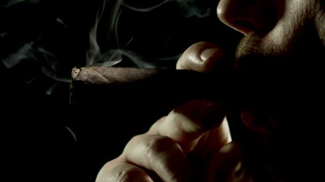 cigar smoker on black-slowmo-1080hd - puro stok videoları ve detay görüntü çekimi