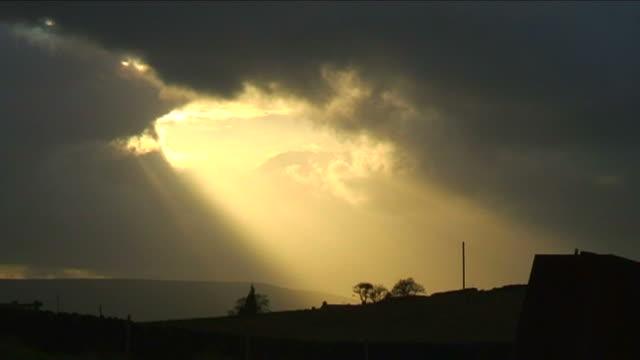 stockvideo's en b-roll-footage met sunshine through dark clouds - regen zon