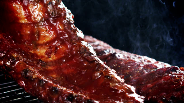 BBQ SPARERIBS- SLOW MOTION CU of spareribs laid on outdoor grill. Shot with the RED EPIC camera in slow motion in 1080 HD. pork stock videos & royalty-free footage