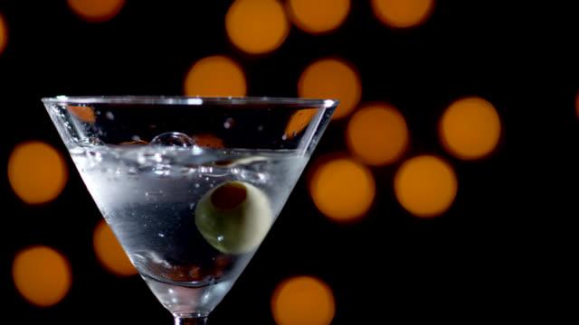martini with olive dropped-slow motion - martini bildbanksvideor och videomaterial från bakom kulisserna