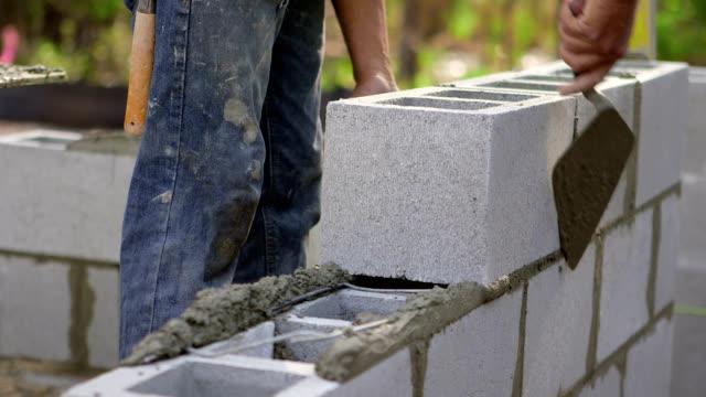 vídeos de stock e filmes b-roll de trabalhador da construção civil-blocos de cinzas - cinza