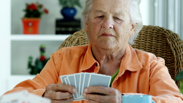 ELDERLY WOMAN PLAYING CARDS Elderly woman playing cards with a friend. medicare stock videos & royalty-free footage