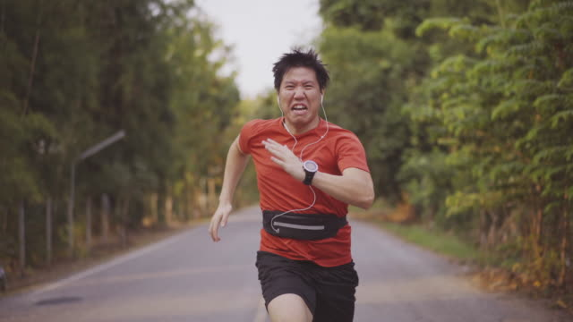 4K CU Male Sprinter Asian man sprinter running in nature route exhaustion stock videos & royalty-free footage