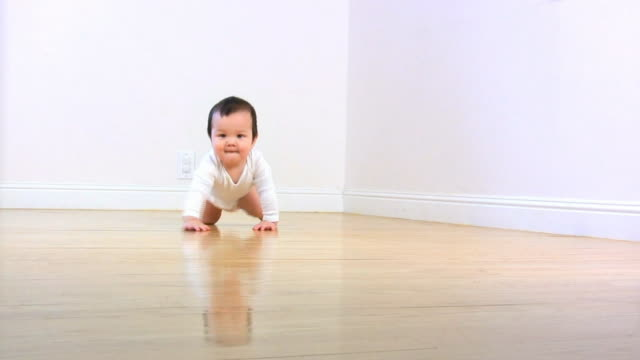 BABY CRAWL WHITE (HD) A baby boy crawls across the floor against white walls. crawling stock videos & royalty-free footage