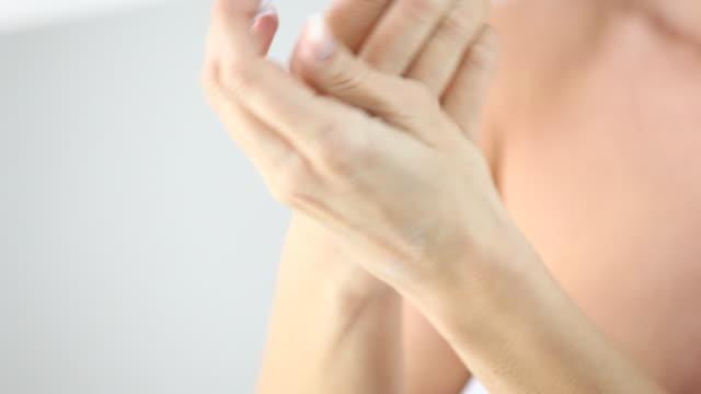 vidéos et rushes de hd 1080: femme appliquer la crème hydratante ont mains. - dermatologie