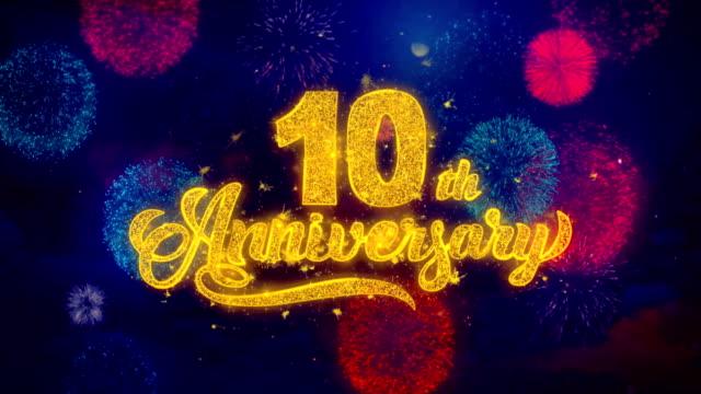 vídeos y material grabado en eventos de stock de 10o feliz aniversario saludo texto sparkle partículas en fuegos artificiales de colores - aniversario