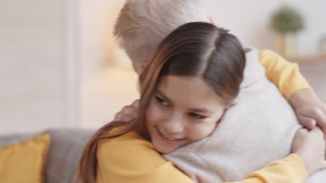 10-Year-Old Caucasian Girl Hugging Granny on Couch at Home Chest-up shot of happy young Caucasian girl with long dark hair giving her granny loving embrace while visiting her at home granddaughter stock videos & royalty-free footage