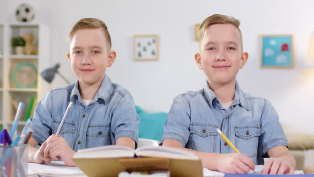 10-year-old caucasian twins studying and posing for camera - gemelle video stock e b–roll