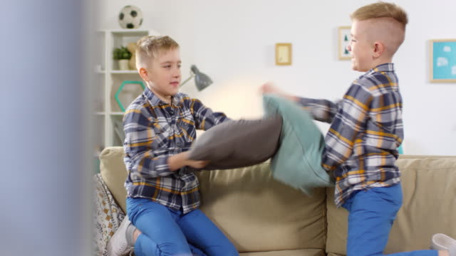 10-year-old twins having vigorous pillow fight - gemelle video stock e b–roll